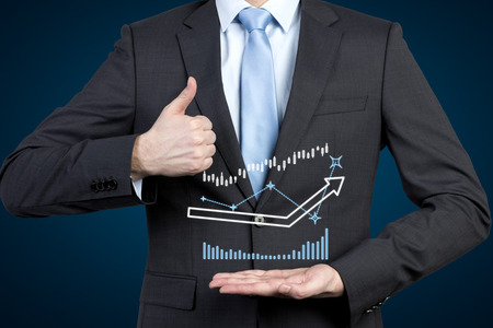 businessman holding drawing charts and showing  thumb up photo