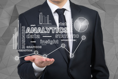 gripping bars: businessman holding analytics symbol on black background