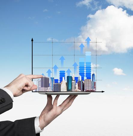 crecimiento: Mano que sostiene la tableta digital con el aislamiento gr�ficos en el cielo