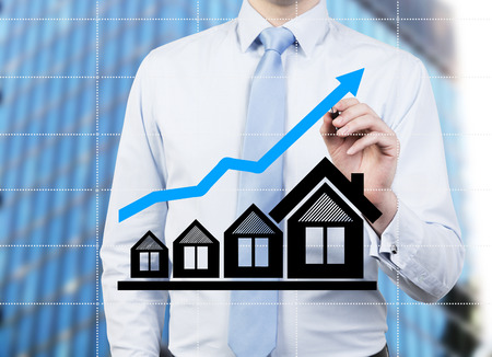 gripping bars: young businessman drawing blue chart over house Stock Photo