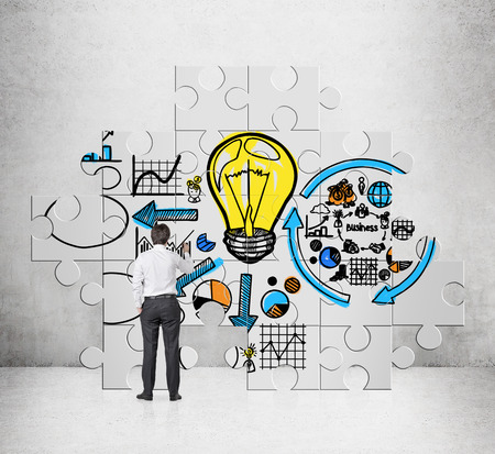 business development: businessman drawing business startegy on puzzle