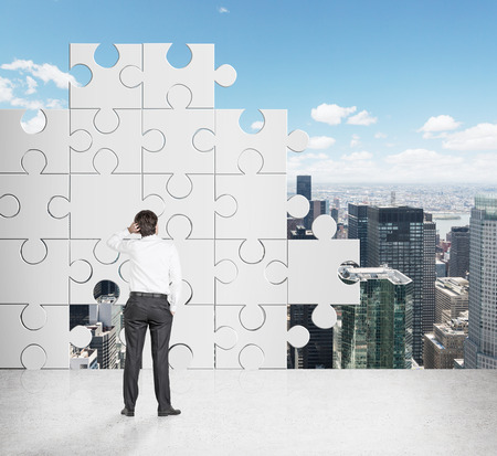 businessman looking on puzzle wall photo