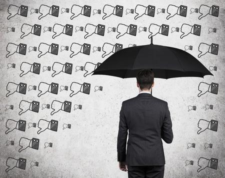 pollice in gi: uomo d'affari con l'ombrello e il pollice verso il basso la pioggia Archivio Fotografico