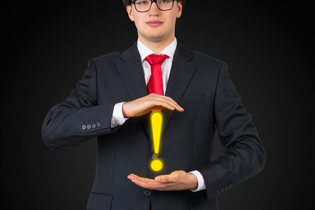 emphasis: businessman holding exclamation mark, close up