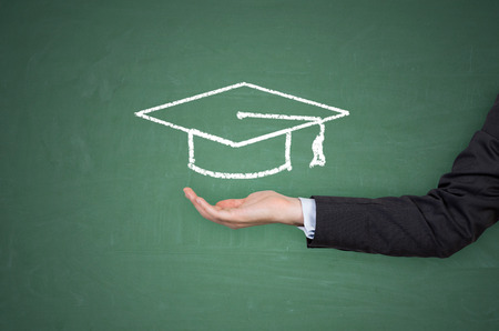 bachelor s degree: hand holding bachelor hat on green background Stock Photo
