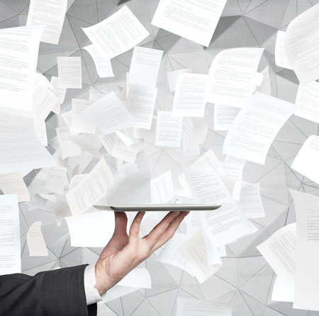 clerical: hand holding tablet in office and falling papers Stock Photo