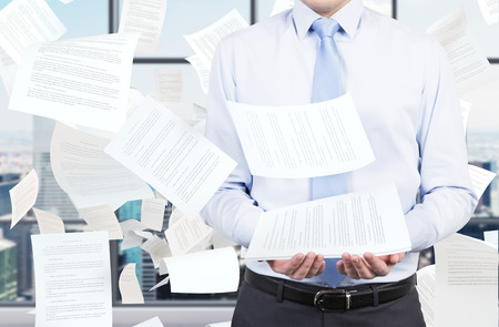 clerical: young businessman and falling papers
