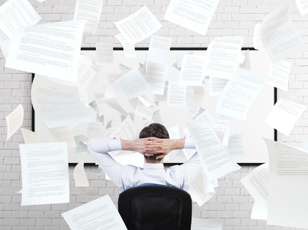 disarray: young businessman sitting in office and falling papers