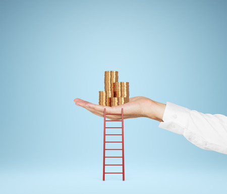 hand holding gold coins with ladder  isolation on blue photo