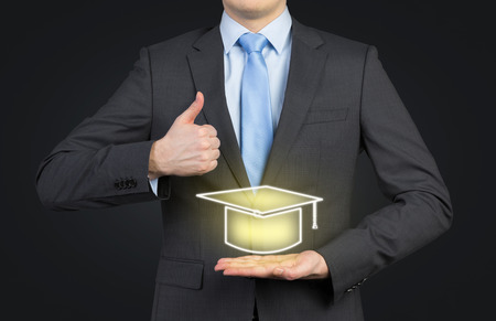 graduate students: businessman showing thumb up and holding hat bachelor