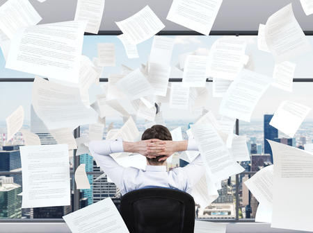 clerical: young businessman sitting in office and falling papers
