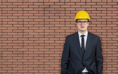 executive helmet: businessman in hard hat on brick wall background