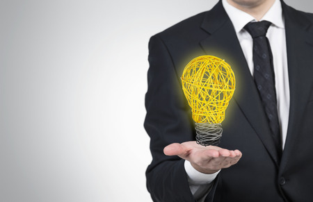 lightbulb: businessman holding lightbulb of wire on a gray background Stock Photo