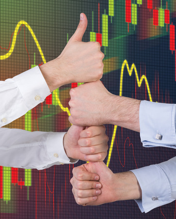Hands showing thumb up  and stock graph on virtual screen photo