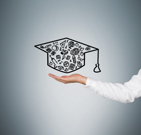 alumnus: hand holding business symbol in form bachelor cap Stock Photo