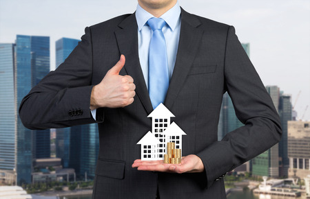 cottage house: businessman showing thumb up and holding paper home and coin