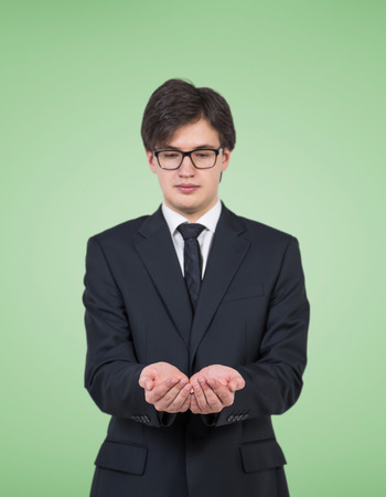 invisible object: businessman in suit holding invisible object on green background Stock Photo