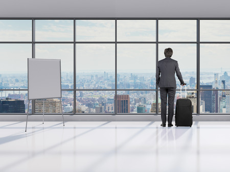 businessman with briefcase in office looking to window photo