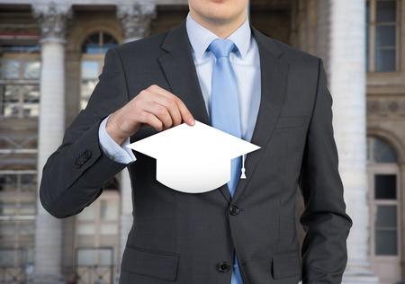 alumnus: student holding hat bachelor sitting in office Stock Photo