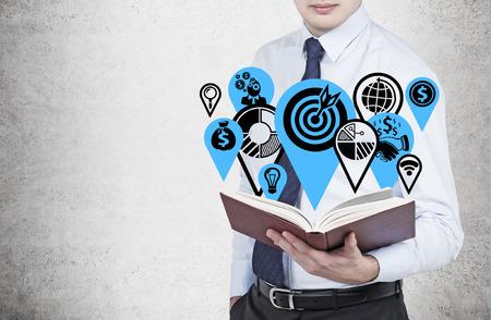 estrategia: hombre de negocios la celebraci�n de libro con iconos de negocios Foto de archivo