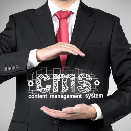 content management: businessman holding drawing cms symbol in hand