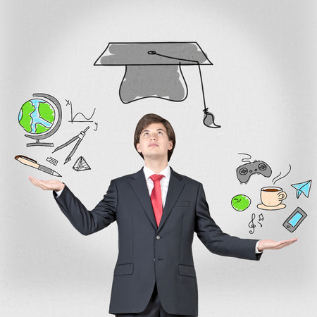 graduation suit: student holding planet, bachelor hat and education symbols Stock Photo
