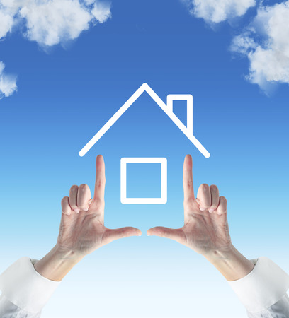 house in hand: two hands showing house on sky background