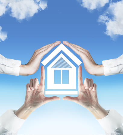 four hands: four hands holding house on sky background Stock Photo