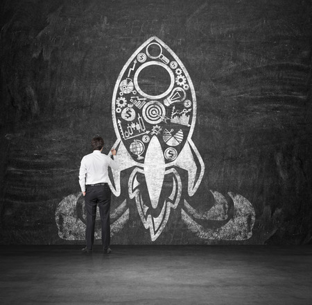rocket man: businessman drawing rocket with business icons on concrete wall