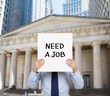 need: businessman holding placard with need a job Stock Photo