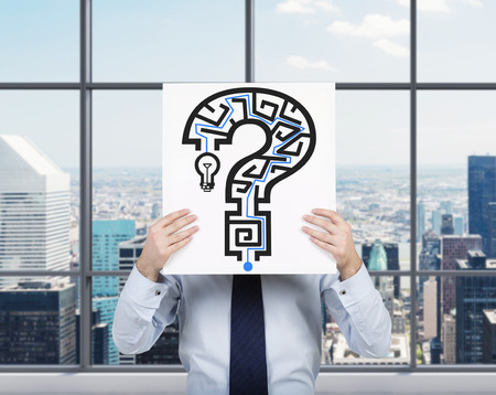 question marks: businessman holding placard with drawing question mark maze