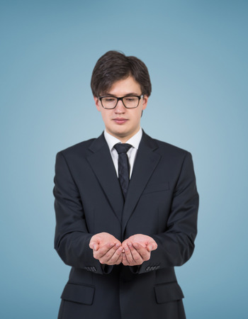 invisible object: businessman in suit holding invisible object on blue background Stock Photo