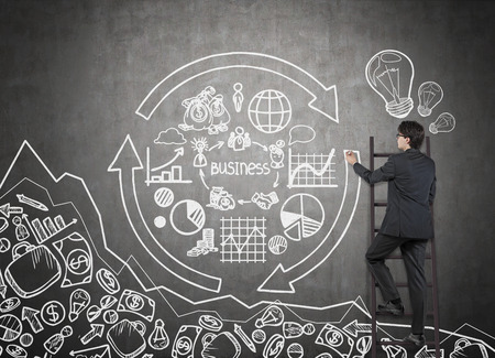 marketing goals: businessman on ladder drawing business chart and symbol