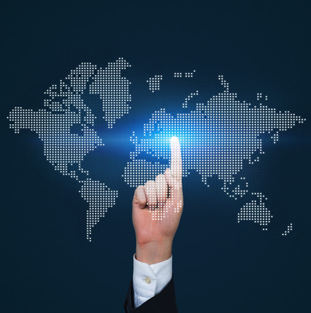virtual world: hand pushing virtual world map on blue background