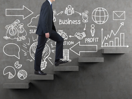 businessman walking on stairs and drawing business strategy on wall