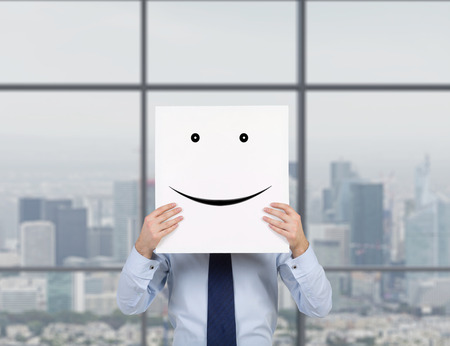 success symbol: businessman holding poster with drawing smile Stock Photo