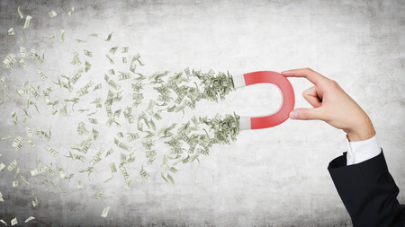 hand attracts money with a large red magnet Archivio Fotografico