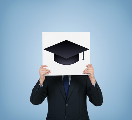 alumnus: businessman holding poster with bachelor hat isolation on blue