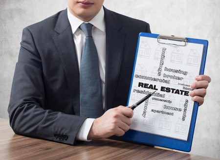 symbols commercial: businessman in suit holding clipboard with real estate concept