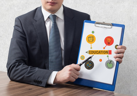 graduation suit: businessman in office holding clipboard with education symbol