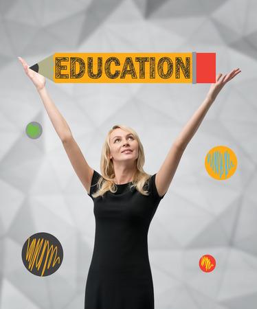 alumnus: happy woman holding big pencil, education concept