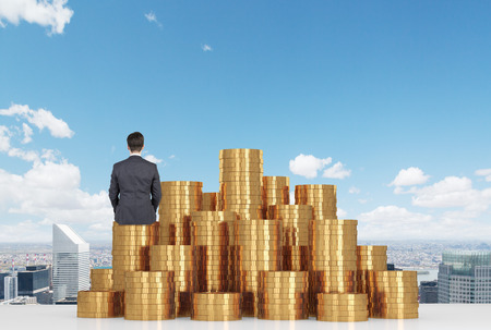 rich: businessman sitting on gold coins on table and looking to city