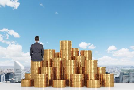 prosperidad: hombre de negocios sentado en monedas de oro sobre la mesa y mirando a la ciudad Foto de archivo