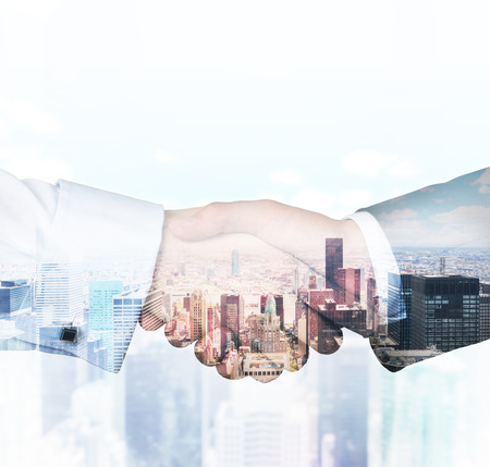 handshake on a building background, double exposure Imagens
