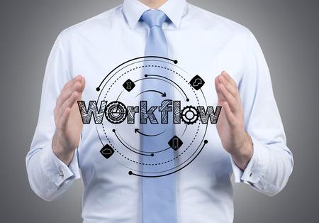 initiate: businessman holding workflow scheme in hands