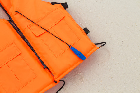 orange life jacket on sand