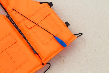 lifejacket: orange life jacket on sand