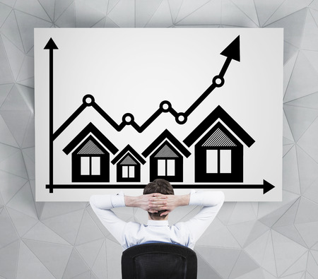 mortgage rates: businessman looking at drawing real estate icons and chart