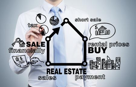 青の背景に不動産の概念を描くビジネスマン