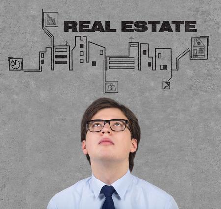 realtor: realtor looking at drawing real estate icon on wall Stock Photo